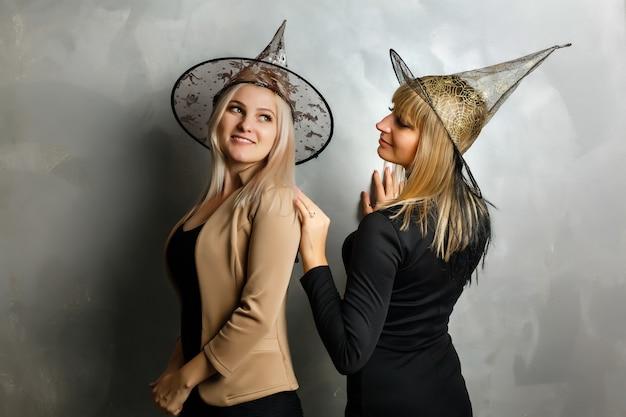 Portret van twee gelukkige jonge vrouwen in de zwarte kostuums van heksenhalloween gedeeltelijk