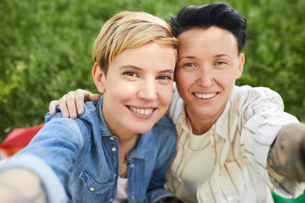 Portret van twee gelukkige lesbiennes glimlachen die zij selfie portret nemen terwijl ze buiten zitten