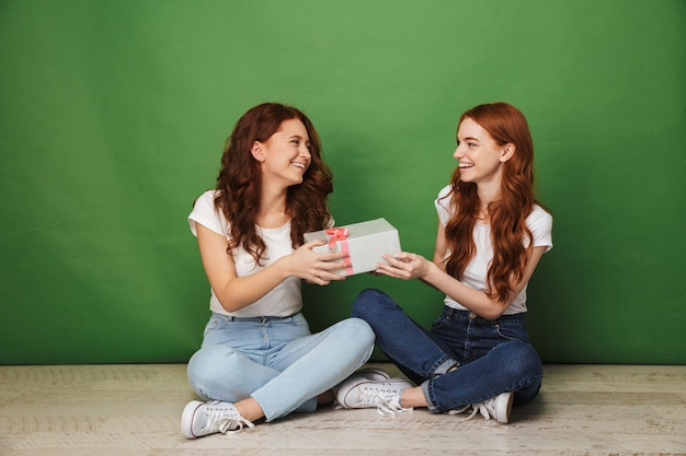 Portret van twee gelukkige meisjes 20s met gember haar in vrijetijdskleding zittend op de vloer met gekruiste benen en met huidige doos, geïsoleerd op groene achtergrond