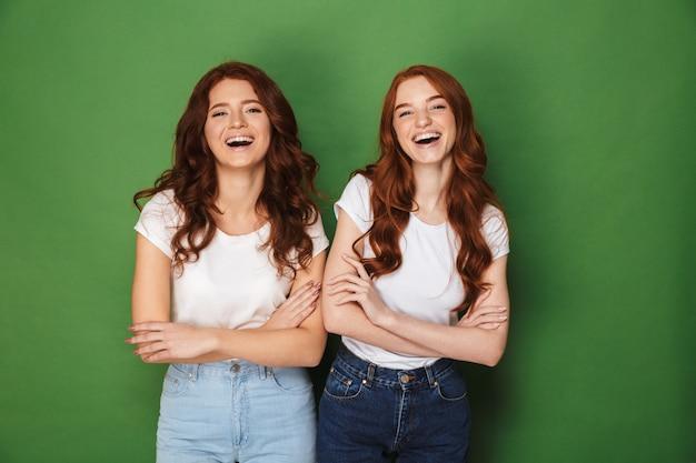 Portret van twee gelukkige meisjes 20s met gemberhaar in vrijetijdskleding die bij camera met gekruiste wapens glimlachen, die over groene achtergrond wordt geïsoleerd