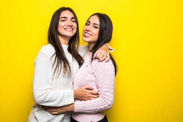 Portret van twee gelukkige meisjes gekleed in truien knuffelen geïsoleerd over gele muur