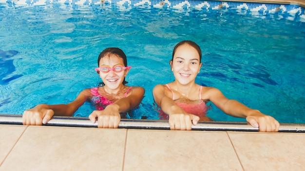 Portret van twee gelukkige meisjesvrienden die in binnenzwembad poseren