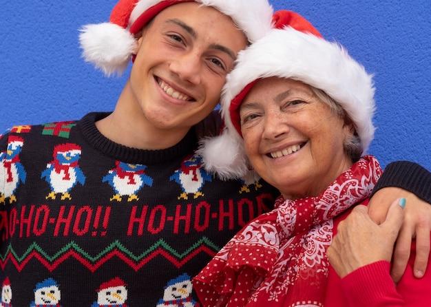 Portret van twee gelukkige mensen, grootmoeder en kleinzoon met een kerstmuts en kersttrui, die elkaar met liefde omhelzen en glimlachend naar de camera kijken. positieve emotie en familieconcept