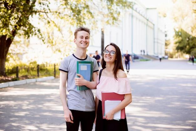Portret van twee gelukkige studenten die zich in park dichtbij universiteit met boeken, oefenboeken bevinden