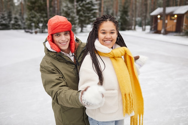 Portret van twee gelukkige vrienden glimlachen naar de camera terwijl ze buiten in de winterdag staan
