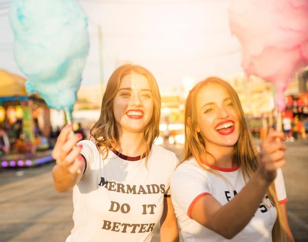 Portret van twee gelukkige vrouwelijke vrienden die suikergoedzijde houden