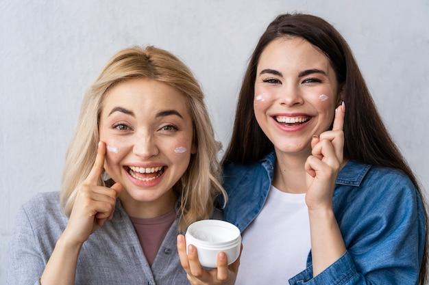 Portret van twee gelukkige vrouwen die en met vochtinbrengende crème lachen spelen