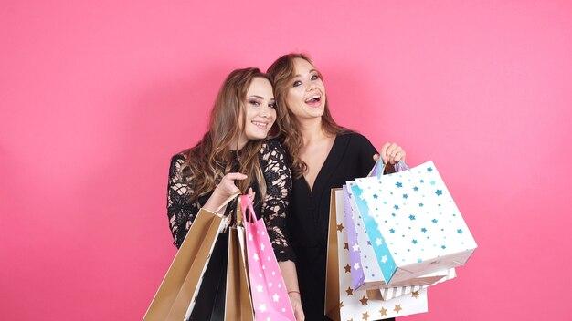 Portret van twee gelukkige vrouwen met aankopen in hun handen