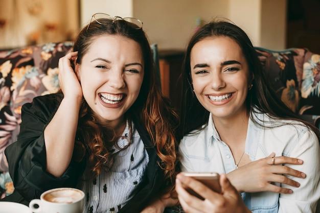 Portret van twee geweldige vriendinnen kijken camera lachen terwijl koffie drinken in een coffeeshop en smartphones gebruiken.