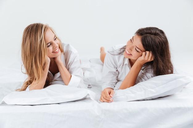 Portret van twee glimlachende jonge vrouw die ligt en elkaar aankijkt op een wit bed