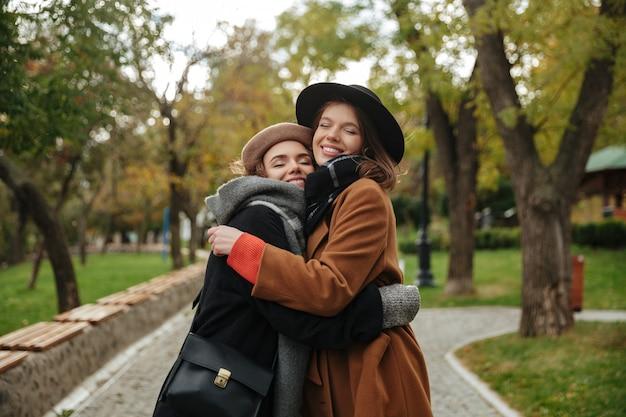 Portret van twee glimlachende meisjes gekleed in de herfstkleren het koesteren