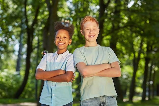 Portret van twee glimlachende tienerjongens die zich in park in openlucht samen met zeepbellen op voorgrond bevinden