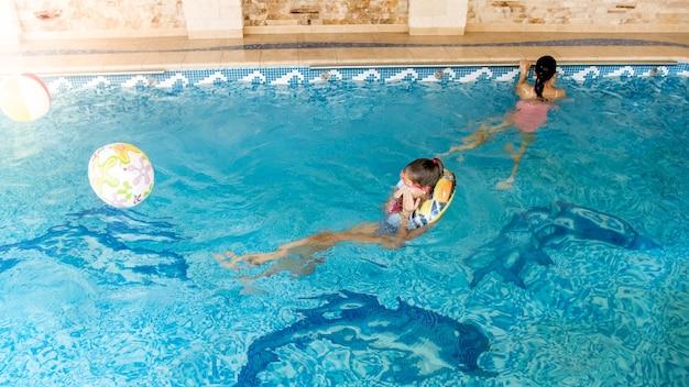 Portret van twee glimlachende tienermeisjes die in het zwembad van de sportschool zwemmen