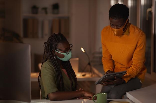 Portret van twee hedendaagse afro-amerikaanse mensen die maskers dragen in kantoor terwijl ze laat in een donkere kantoor werken