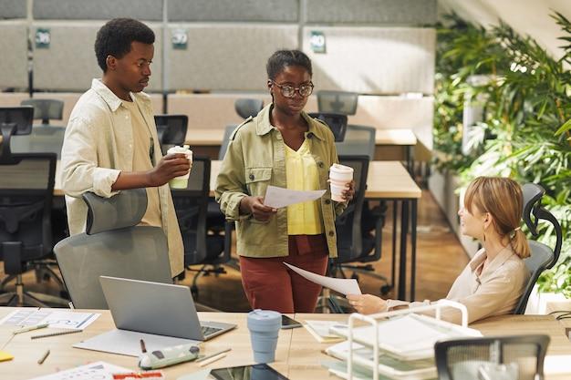 Portret van twee hedendaagse afro-amerikaanse mensen gekleed in vrijetijdskleding praten met collega tijdens het werken op kantoor, kopie ruimte