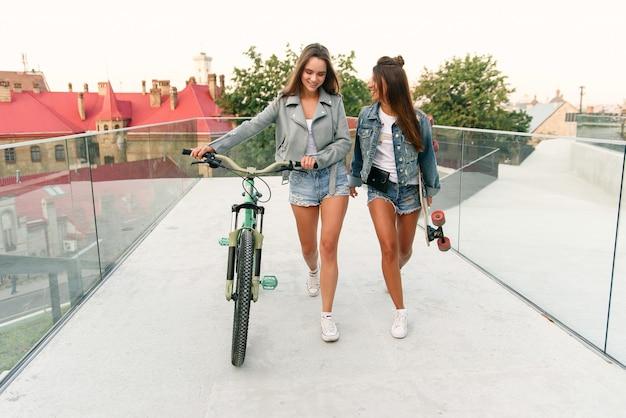 Portret van twee jonge aantrekkelijke stedelijke vrouwen lopen met een fiets en skateboarden op straat in zonnige zomerdag. slow motion.
