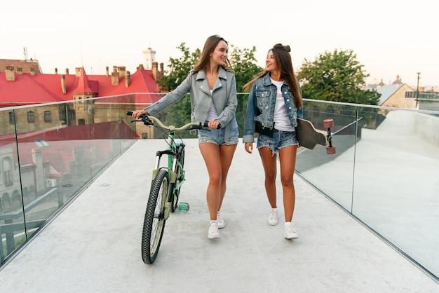 Portret van twee jonge aantrekkelijke stedelijke vrouwen lopen met een fiets en skateboarden op straat in zonnige zomerdag.