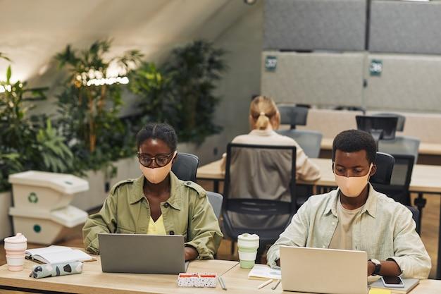 Portret van twee jonge afro-amerikaanse mensen die maskers dragen tijdens het werken aan een bureau in een postpandemisch kantoor, kopie ruimte