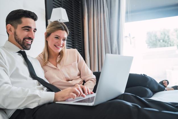 Portret van twee jonge bedrijfsmensen die aan laptop in de hotelkamer samenwerken. zakelijke reizen concept.
