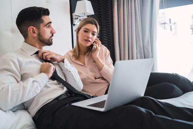 Portret van twee jonge bedrijfsmensen die aan laptop in de hotelkamer samenwerken.