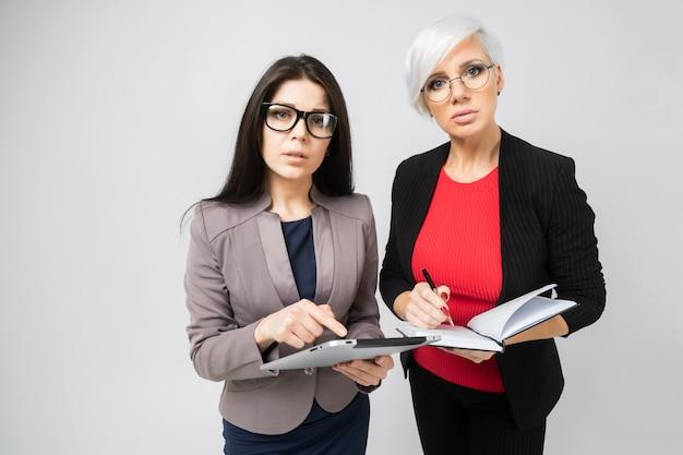 Portret van twee jonge geïsoleerde bedrijfsdames in kostuums
