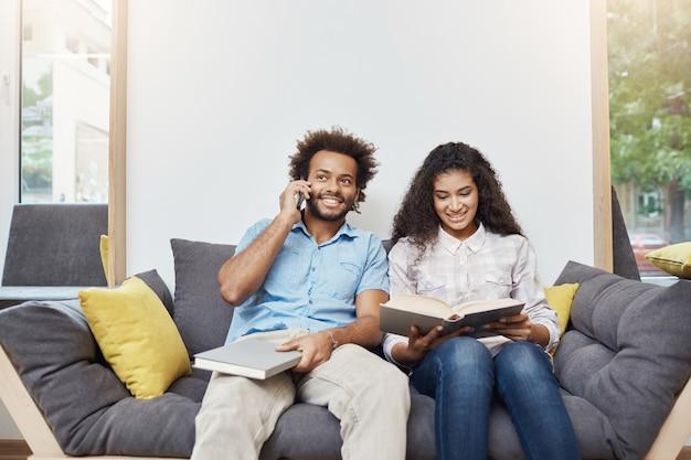 Portret van twee jonge knappe donkere studenten in vrijetijdskleding die samen op bank in moderne bibliotheek zitten, boeken lezen, examens voorbereiden, o telefoon spreken.