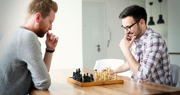 Portret van twee jonge man die aan het schaken is