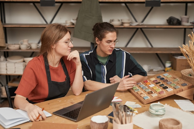 Portret van twee jonge mensen die kleine bedrijven beheren terwijl ze aan een houten tafel werken met een laptop in een pottenbakkerij, kopieer ruimte