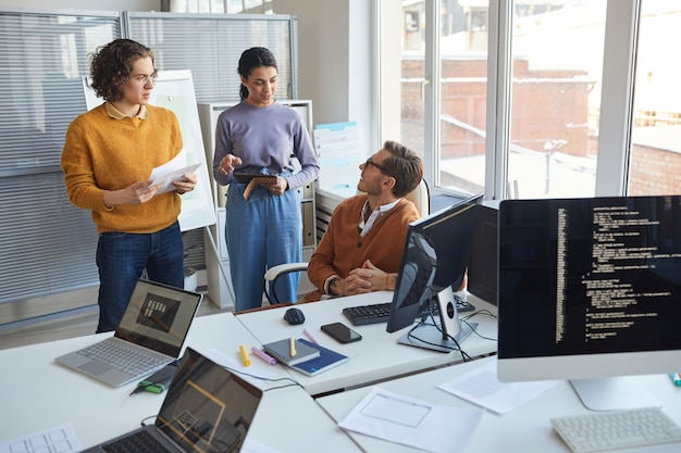 Portret van twee jonge mensen die praten met een mannelijke manager tijdens het bespreken van een softwareontwikkelingsproject in een modern kantoor, kopieer ruimte