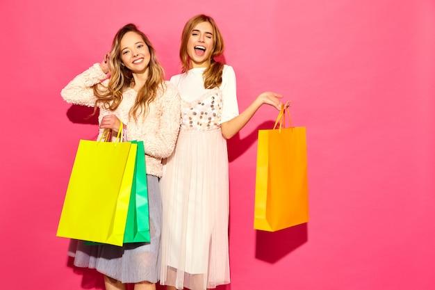 Portret van twee jonge modieuze glimlachende blonde vrouwen die het winkelen zakken houden. vrouwen gekleed in zomer hipster kleding. positieve modellen die zich voordeed op roze muur
