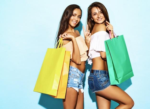 Portret van twee jonge modieuze glimlachende donkerbruine vrouwen die het winkelen zakken houden. vrouwen gekleed in zomer hipster kleding. positieve modellen die zich voordeed op blauwe muur