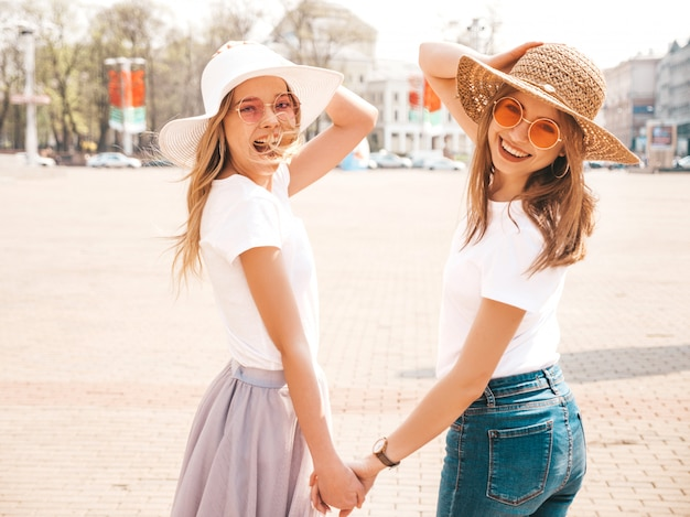 Portret van twee jonge mooie blonde glimlachende hipster meisjes in kleren van de trendy de zomer witte t-shirt. . positieve modellen houden elkaars hand vast