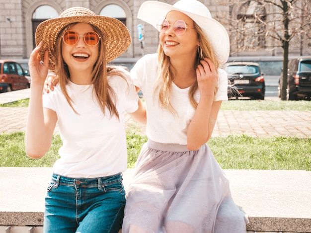 Portret van twee jonge mooie blonde glimlachende hipster meisjes in kleren van de trendy de zomer witte t-shirt.
