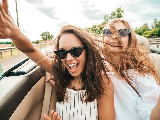 Portret van twee jonge mooie en glimlachende hipstermeisjes in convertibele auto