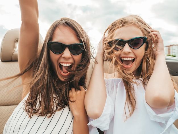 Portret van twee jonge mooie en glimlachende hipstervrouwen in convertibele auto