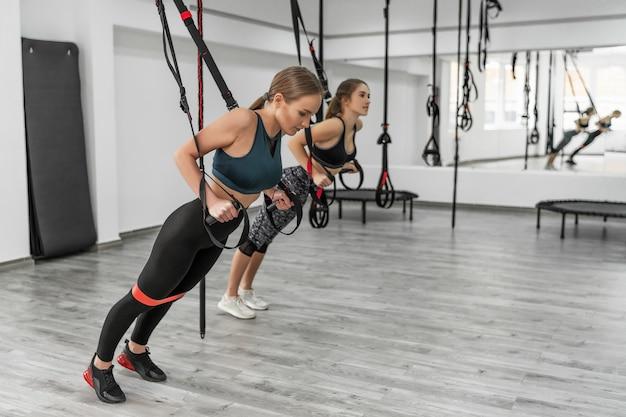 Portret van twee jonge mooie fit vrouwen in sportkleding training armen met trx fitness riemen in de sportschool