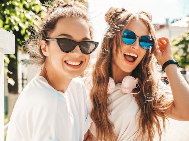 Portret van twee jonge mooie glimlachende hipster-vrouwen in trendy zomerse witte t-shirtkleren