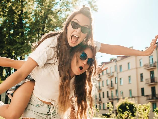 Portret van twee jonge mooie glimlachende hipstermeisjes in trendy zomerse witte t-shirtkleren