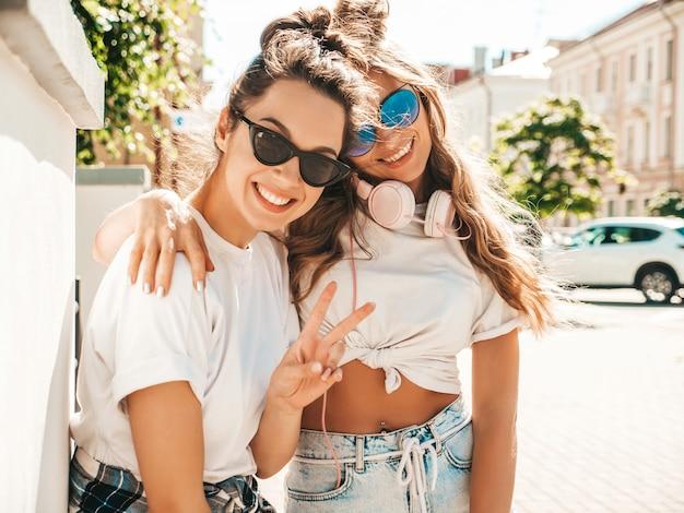 Portret van twee jonge mooie glimlachende hipstervrouwen in trendy zomerse witte t-shirtkleren