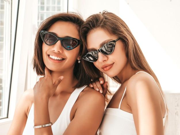 Portret van twee jonge mooie glimlachende vrouwen in witte lingerie
