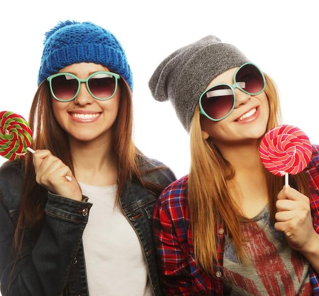 Portret van twee jonge mooie hipstermeisjes die hoeden en zonnebrillen dragen die snoepjes houden. studioportret van twee vrolijke beste vrienden die plezier hebben en grappige gezichten trekken.