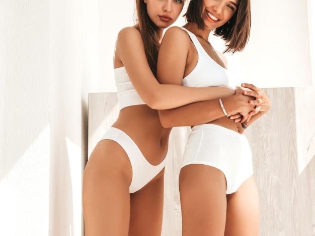 Portret van twee jonge mooie lachende meisjes in witte lingerie