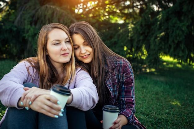 Portret van twee jonge mooie meisjes zitten naast elkaar op het groene gazon in het park