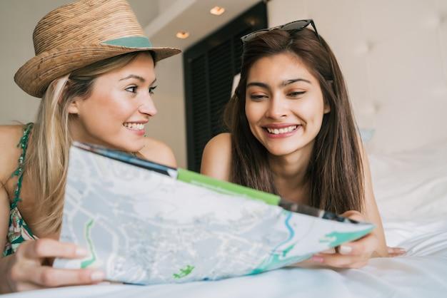 Portret van twee jonge reizigersvrienden die wat tijd doorbrengen en hun reis organiseren in hotelkamer. reis- en levensstijlconcept.