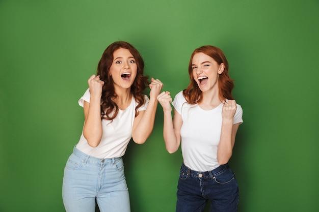 Portret van twee jonge roodharige vrouwen 20s in vrijetijdskleding die zich verheugen en vuisten balde, geïsoleerd op groene achtergrond