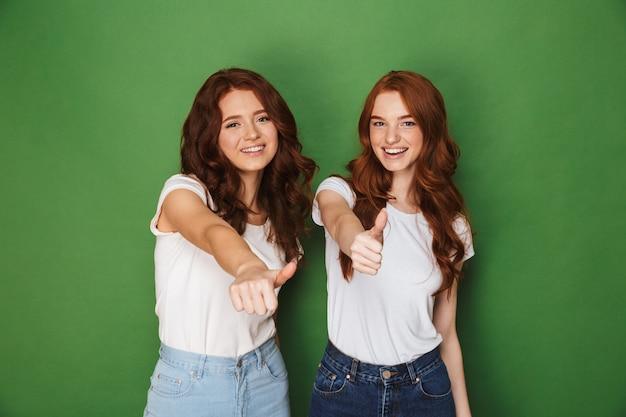 Portret van twee jonge roodharige vrouwen 20s in vrijetijdskleding glimlachen naar de camera en duimen opdagen, geïsoleerd op groene achtergrond
