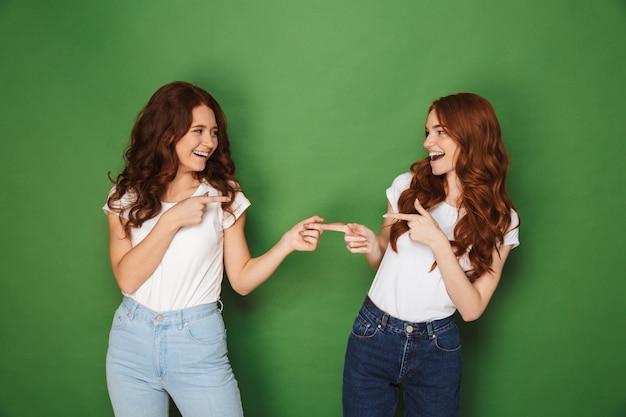 Portret van twee jonge roodharige vrouwen 20s in vrijetijdskleding glimlachend en wijzende vingers naar elkaar, geïsoleerd op groene achtergrond