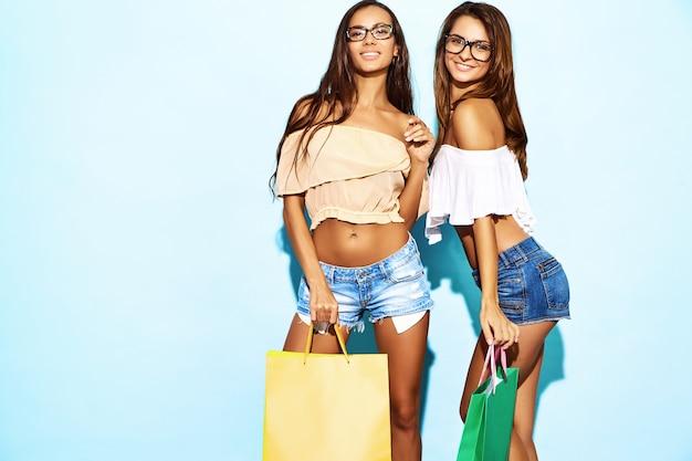 Portret van twee jonge sexy modieuze glimlachende donkerbruine vrouwen die het winkelen zakken houden. vrouwen gekleed in zomer hipster kleding. positieve hete modellen die over blauwe muur stellen
