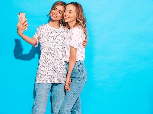 Portret van twee jonge stijlvolle glimlachende blonde vrouwen. meisjes gekleed in zomer hipster kleding. positieve modellen die selfie op smartphone dichtbij blauwe muur in studio maken