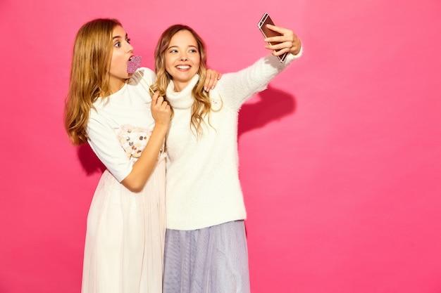 Portret van twee jonge stijlvolle glimlachende blonde vrouwen